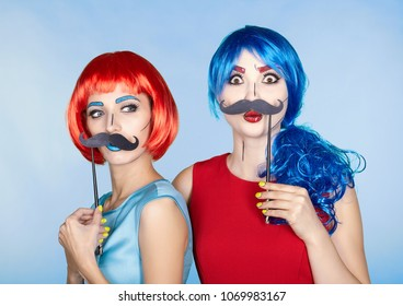 Portrait of young women in comic pop art make-up style. Females in red and blue wigs on blue background. Girls with false moustashes in hands