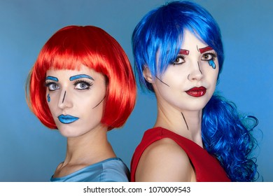 Portrait of young women in comic pop art make-up style. Females in red and blue wigs on blue background.