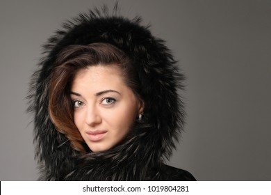 Portrait of a young women with a deep look. Dressed in natural fur. Natural makeup, green eyes and lightly curling hair.