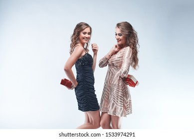 Portrait of young women friends holding gifts behind the back going to give them each other against white background. Christmas and New Year celebration. Copy space.
