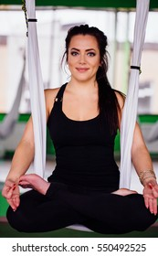 portrait young women making antigravity yoga in the lotus position. Aerial aero fly fitness trainer workout. white hammocks, eco green background studio. meditates. harmony and serenity concept