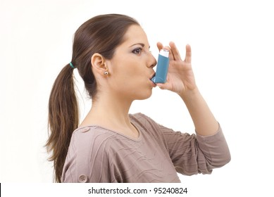 portrait of young women using asthma inhaler