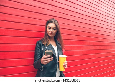 Portrait young women using smart phone isolated on background red wooden  wall .