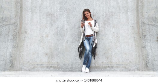 Portrait young women using smart phone isolated on background concrete gray wall .