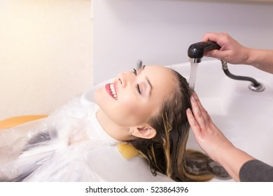 Portrait of young women which wash hair in a beauty salon after hair coloring