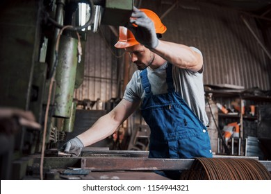 Portrait of a young worker in a hard hat at a large metalworking plant. The engineer serves the machines and manufactures parts for gas equipment.