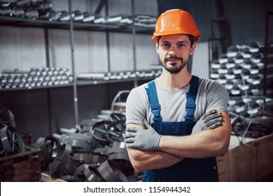 Portrait of a young worker in a hard hat at a large metalworking plant. Shiftman on the warehouse of finished products.