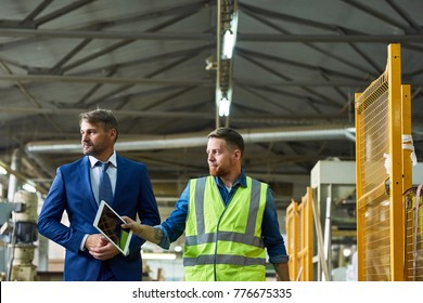 Portrait of young workman giving tour of modern factory to handsome mature businessman discussing possible investment, copy space