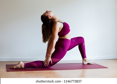 Portrait of young yogi woman practising yoga, wearing sportswear, white studio background, low lunge pose (selective focus)