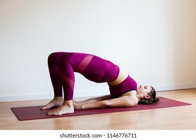 Portrait of young yogi woman practising yoga, wearing sportswear, white studio background, half bridge pose (selective focus)
