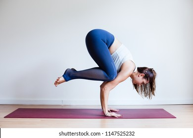 Portrait of young yogi woman practising yoga, wearing blue sportswear, white studio background, crow pose (selective focus)