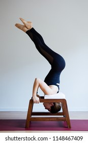 Portrait of young yogi woman practising yoga, wearing black sportswear, white studio background, feet up exercise (selective focus)