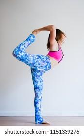 Portrait of young yogi woman practising yoga, wearing colorful sportswear, white studio background (selective focus)