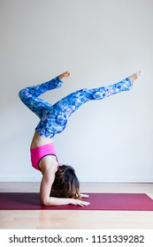 Portrait of young yogi woman practising yoga, wearing colorful sportswear, white studio background, forearm stand pose (selective focus)
