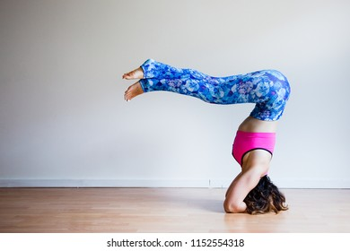 Portrait of young yogi woman practising yoga, wearing colorful sportswear, white studio background,