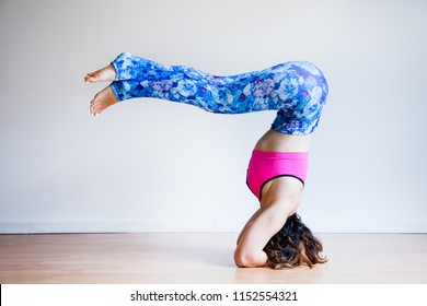 Portrait of young yogi woman practising yoga, wearing colorful sportswear, white studio background, headstand variation (selective focus)