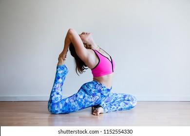Portrait of young yogi woman practising yoga, wearing colorful sportswear, white studio background, king pigeon pose (selective focus)