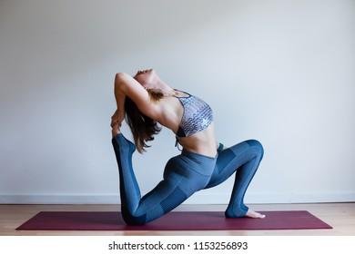 Portrait of young yogi woman practising yoga, wearing blue sportswear, white studio background, king pigeon pose (selective focus)
