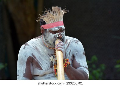 Portrait of a Yugambeh Aboriginal man play Aboriginal  music on didgeridoo, instrument during Aboriginal culture show in Queensland, Australia.