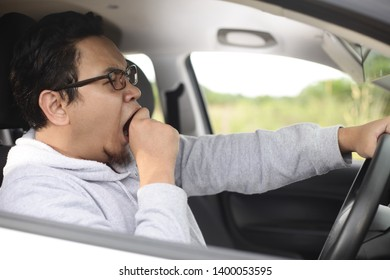 Portrait of yung Asian male driver yawning due to sleepy tired while riding a car, danger traffic accident insurance concept