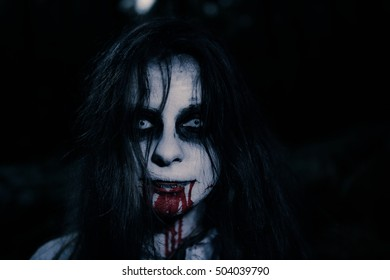 Portrait of zombie girl with white face and black eyes. Blood out of her mouth