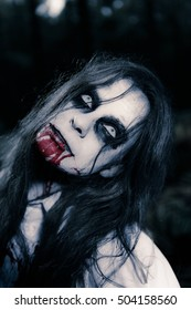 Portrait of zombie girl with white face staring into the light. Blood out of her mouth