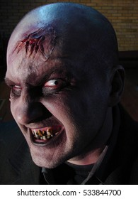 Portrait of a zombie, with open wounds on head and rotten teeth, scary face, film set