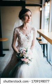portraits of a beautiful bride in a wedding dress at home