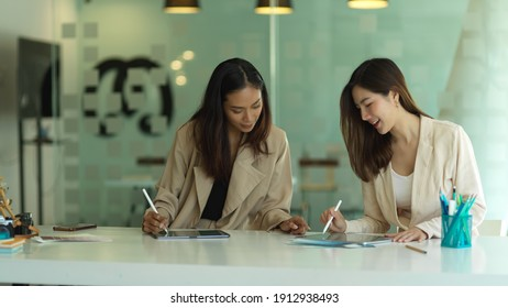 Portraits of businesswomen working together with digital tablet and supplies in modern meeting room