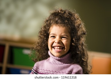 Portraits of children, happy 3 years old female with curly hair smiling for joy in kindergarten
