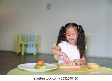 Portraits of happy Asian child girl slicing cucumber vegetable on chopping board at play room. Kid play chef cooking.
