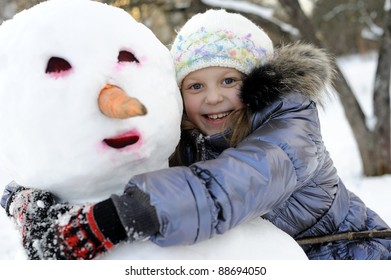 An portraits of happy little girl posing with snowman