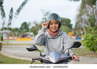 portraits of hijab women open helmet glass and riding motorbikes in a outdoors park on a sunny day