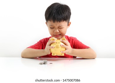 Portraits of little Asian boy looks into a piggy bank, Saving money concept.