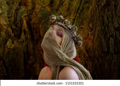 Portraits of a semi-nude woman posing inside a large  hollow oak tree. She is dressed only with rags around her head and wears a thorn wreath on her head. The woman  is seen semi-nude in the photo.