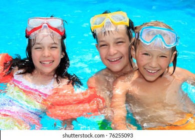 Portraits of three happy children with swimming goggles in a swimming pool.