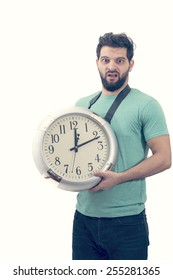 Portraitt of an unhappy male holding big clock running out of time isolated on white background
