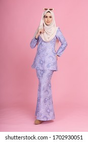 Portraiture of beautiful young Muslim girl wearing light purple dress known as Baju Kurung with hijab. Fashion for dinner, event and Eidul fitri feast.Studio shot with pink background.