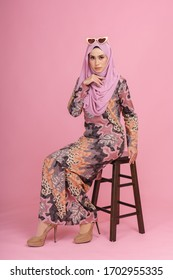 Portraiture of beautiful young Muslim girl wearing batik design dress known as Baju Kurung with hijab. Fashion for dinner, event and Eidul fitri feast. Studio shot with pink background.