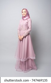 Portraiture of beautiful young Muslim girl wearing hijab and dress known as Baju Kurung.Fashion for dinner,event and aidilfitri feast.Studio shot with grey background.
