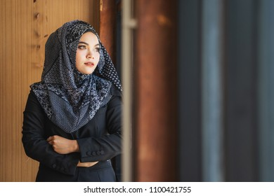 Portraiture of young asian muslim woman in head scarf smile posing for a camera with cafe background