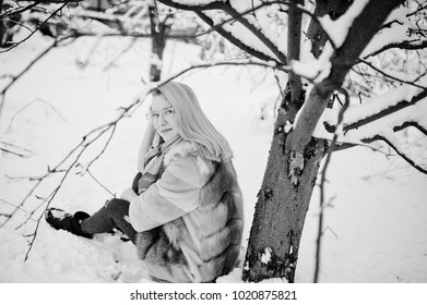 Portraiy of blonde girl in glasses, red fur coat and scarf at winter day.