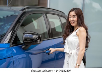 Portrat of Asian customer woman opening the car door when get the new blue color car infront of showroom after purchase the new one,