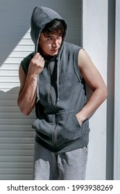 Portrat of Asian handsome man standing holding hand in shirt pocket wearing sleeveless t-shirt gray cover the head sportswear in background - Shutterstock ID 1993938269