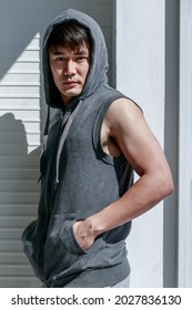 Portrat of Asian handsome man standing holding hand in shirt pocket wearing sleeveless t-shirt gray cover the head sportswear in background - Shutterstock ID 2027836130