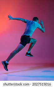 Portrat of Caucasian professional male athlete, runner training isolated on pink studio background with blue neon filter, light. Concept of action, motion, speed, healthy lifestyle. Copyspace for ad. - Shutterstock ID 2027515016