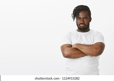 Portrat of offended gloomy dark-skinned guy with beard and moustache holding hands crossed on chest, sulking and looking from under forehead, being insulted and waiting for apologies