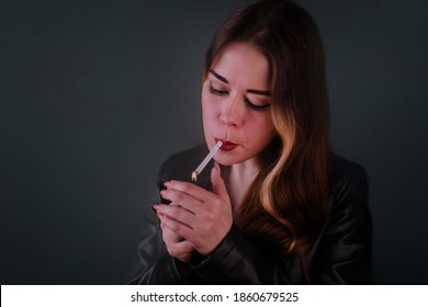 Portrat of young beautiful woman lighting h``er cigarette while looking down. She wears black leather jacket, her hair is loose. Dark abstract background. - Shutterstock ID 1860679525