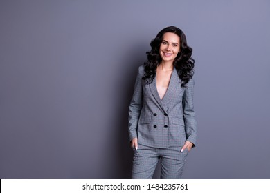 Portraut of beautiful woman with beaming smile standing wearing gray suit trousers pants isolated over gray background