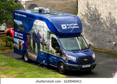 PORTREE, SCOTLAND - AUGUST 4, 2019: Blue Ford Transit light commercial vehicle of Royal Bank of Scotland chraged by electricity used for mobile banking services